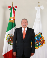 photo of Egidio Torre-Cantu standing in front of two flags