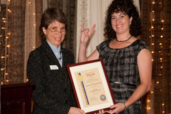Susana Hildebrand smiling, doing hook 'em horns hand, receiving award